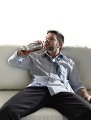 drunk businessman drinking whiskey bottle in couch