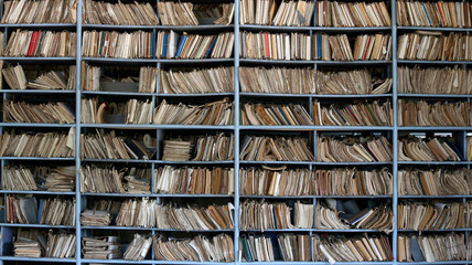 shelves full of files in a messy old-fashioned archive