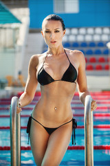 Beautiful young woman posing by the pool