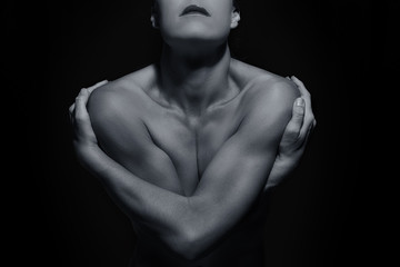 Body scape of woman front with arms crossed in low light emotion