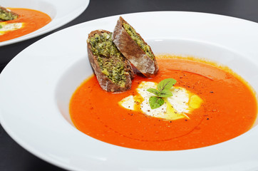 Tomato soup with basil, cream and baguette with herb butter