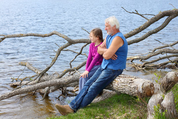 Grandfather and granddaughter are dreaming in nature
