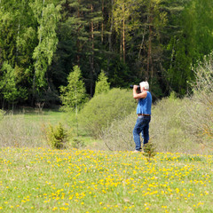 Old  man photographer photographing in nature