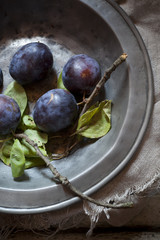 whole purple prunes with branches and leafs on vintage plate
