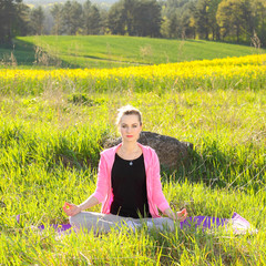 Beautiful woman practices yoga in nature