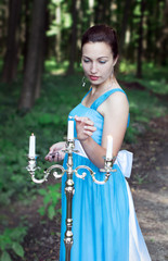 girl sets fire three candles on a silver candlestick in a forest