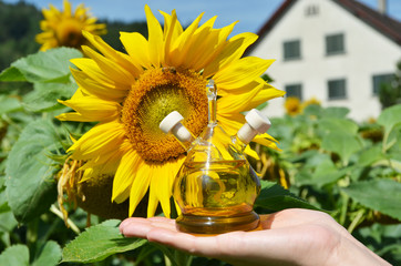 Bottle of oil against sunflowers