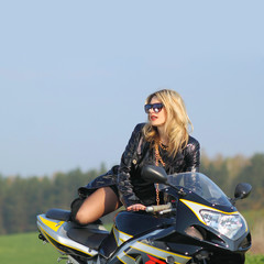Portrait of a beautiful blonde woman on a sports motorcycle