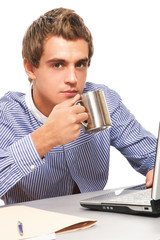 Portrait of young man holding cup, sitting on the desk