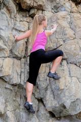 Beautiful woman alpinist is climbing on a mountain