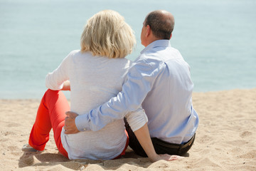 Mature lovers sitting on beach