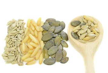 Pine nuts, sunflower, pumpkin seeds with wooden spoon