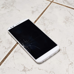 Broken smart phone over the tiles