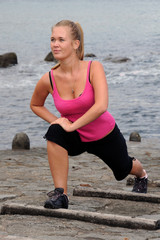 Pretty young woman doing sport exercises by the sea