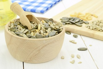 A mixture of seeds and pine nuts in a bowl on wooden table