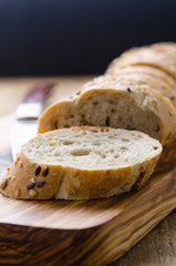 bread with seeds on a wooden board and knife