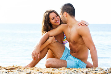 Handsome guy and pretty girlfriend resting on sand