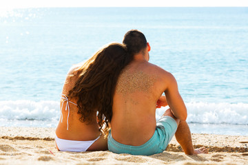 Rear view   couple sitting at  beach