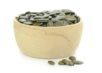 A wooden bowl of pumpkin seeds on a white background