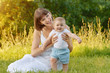 mother with baby on green grass