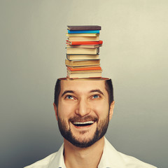 man looking up at books in the head