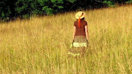 Hippie woman with guitar walking in summer meadow - close up