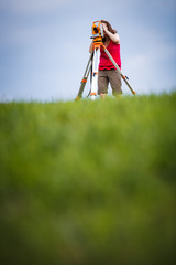 Young, female land surveyor at work - using the theodolite level