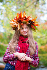 Girl in colorful autumnal wreath