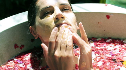 Woman putting mask on her face in the spa and relaxing