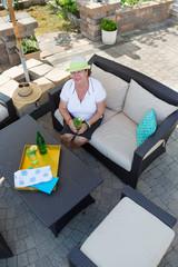 Stylish senior woman drinking on a patio