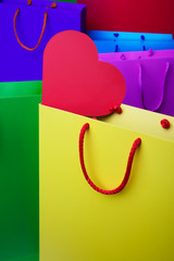 Colourful paper shopping bags with red heart.
