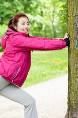 Girl stretching beside tree