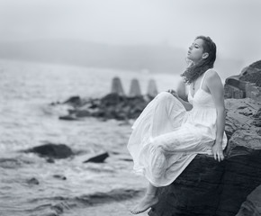 Woman sitting and looks into the distance at sea.