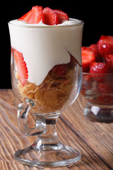 yogurt with strawberries and cornflakes in a glass vertical