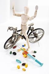 Holzfigur als Radfahrer in Vordergrund Pillen und Spritze