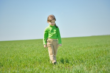 Little girl walks in a field.
