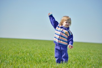 Little girl with raised hand in a field