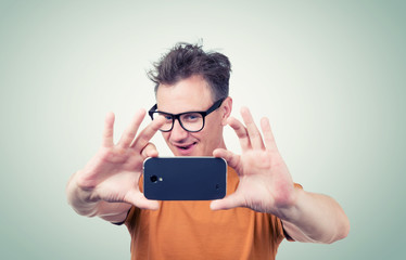 Funny man in glasses photographed by smartphone