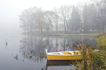 yellow wooden boat on autumn lake and morning mist