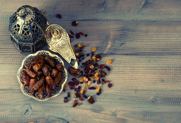 Vintage oriental latern, raisins and dates on wooden background