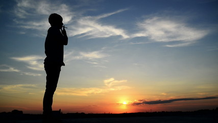 Silhouette of young adult woman smoking a cigarette in sunset.