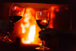 canvas print picture - glass of  wine beside the fire