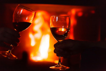 glass of  wine beside the fire
