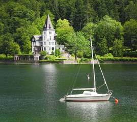 The Grundlsee lake with castle and sailboat. Austria.