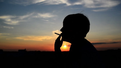 Silhouette of young adult woman smoking a cigarette in sunset