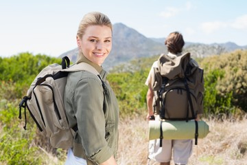 Attractive hiking couple walking on mountain trail woman smiling