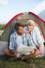 Attractive happy couple sitting by their tent reading map