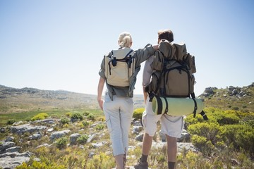 Hiking couple standing on mountain terrain