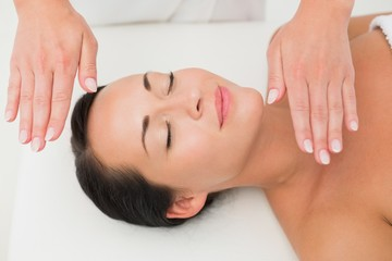 Peaceful brunette getting reiki therapy