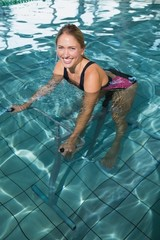 Fit happy blonde using underwater exercise bike